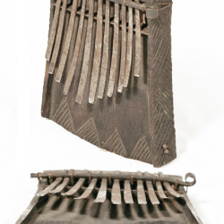 Instrument de musique: bois noir, lamelles métalliques, quatre bruiteurs sur une tringle torsadée (Mozambique)